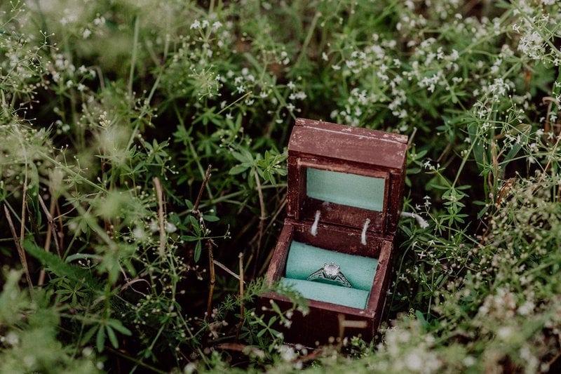 diamantový zásnubný prsteň na saténovej látke v drevenej krabičke na tráve