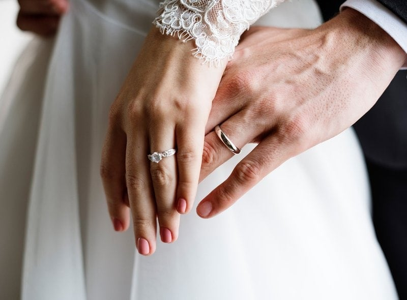 ľavé ruky nevesty a ženícha so zásnubným prsteňom a obrúčkou na prstenníku