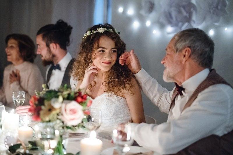 otec a nevesta sedia pri svadobnom stole a emotívne sa rozprávajú
