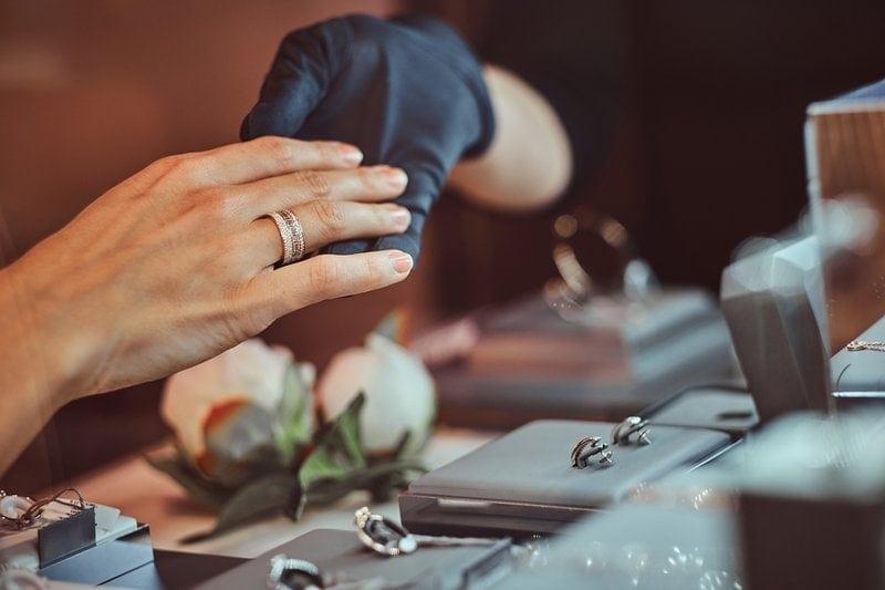 žena si skúša diamantový prsteň v luxusnom klenotníctve