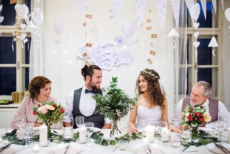 mladomanželia sedia pri svadobnom stole spolu s rodičmi