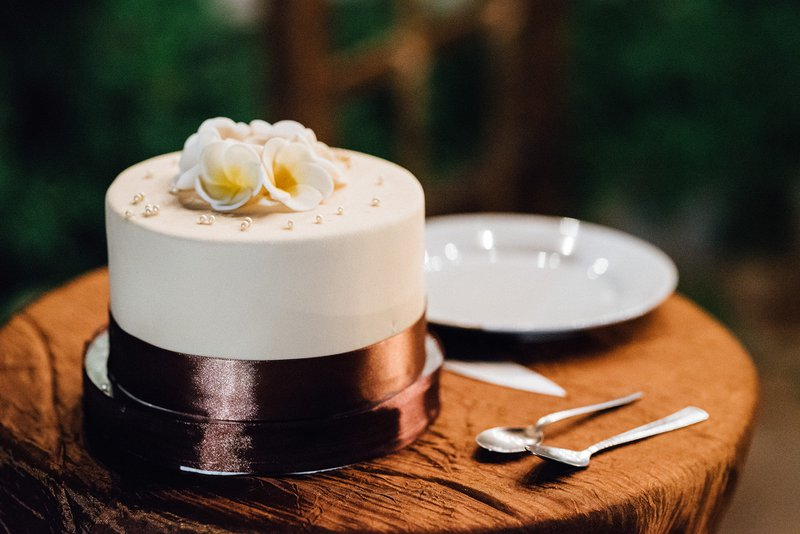 svadobná biela torta s tmavou stuhou uložená na drevenom stolíku