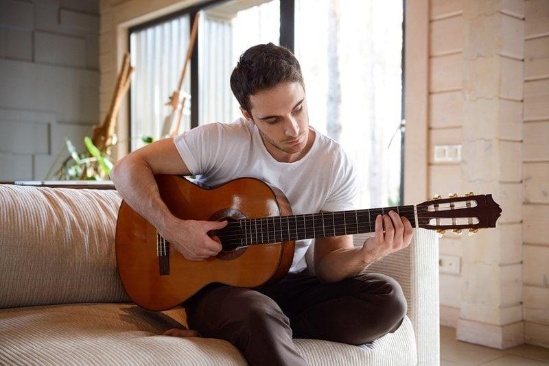 muž skladá pieseň na gitare