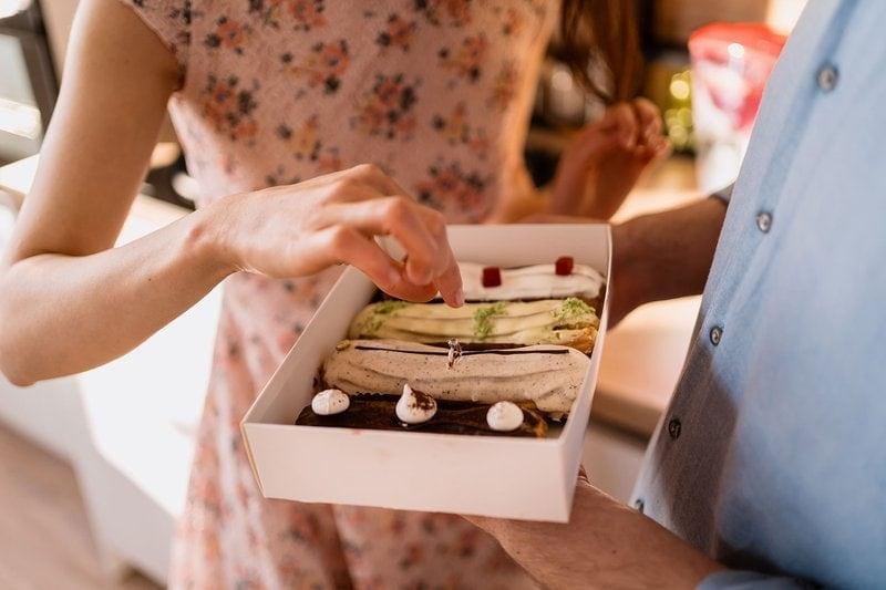 muž žiada partnerku o ruku so zásnubným prsteňom v torte