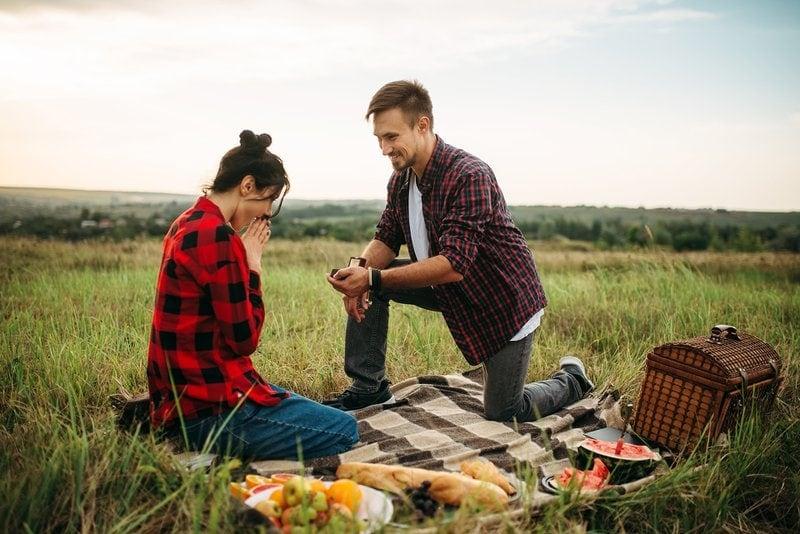 muž žiada o ruku svoju partnerku na pikniku v prírode