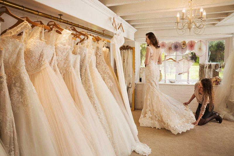 budúca nevesta si v svadobnom salóne vyzerá šaty a asistuje jej pri tom predavačka