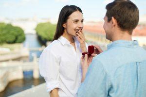 prevkapené a štastné dievča si drží na ústach ruku pri pohľade na priateľa, ktorý ju práve žiada o ruku