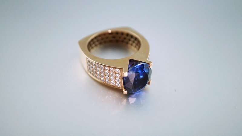 zlatý prsteň s malými diamantmi po bokoch a výrazným zafírom uprostred