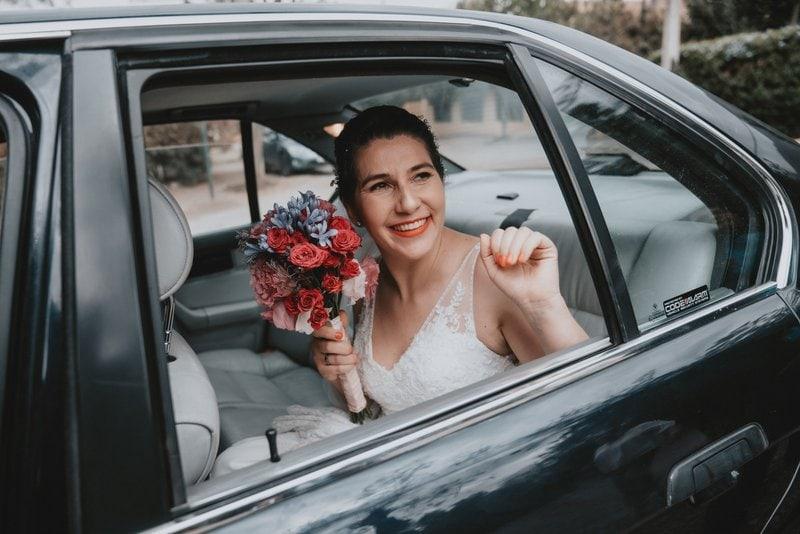 nevesta drží kyticu v ruke a sedí na zadnom sedadle v aute odkiaľ kýva a usmieva sa