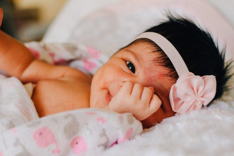 usmievajúce sa bábätko s ružovou čelenou zabalené v deke s veľrybami
