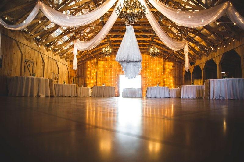 stodola vyzdobená bielymi stuhami a ozdobenými stolmi pripravená na svadobnú hostinu