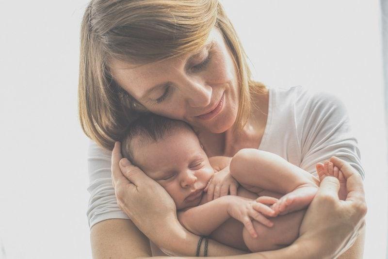 spokojná matka držiaca svoje dieťatko na rukách
