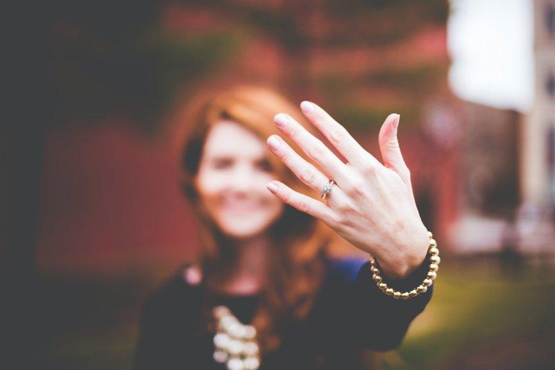 žena s ryšavými vlasmi ukazuje ľavú ruku s detailom na zásnubný prsteň