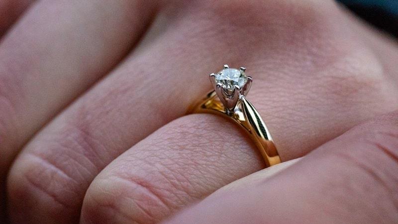 zlatý prsteň s diamantom nastoknutý na prste ruky