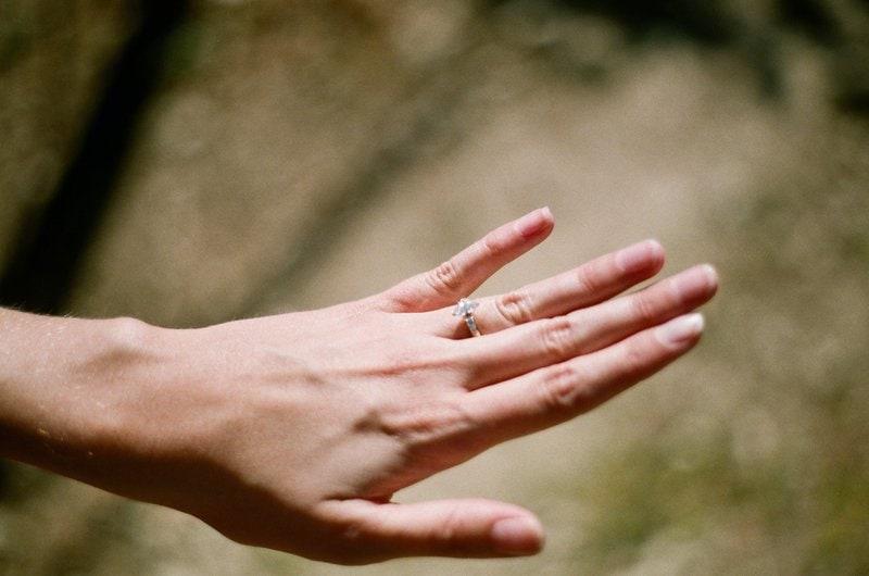 detailný záber na ženskú ľavú ruku s diamantovým prsteňom na prstenníku