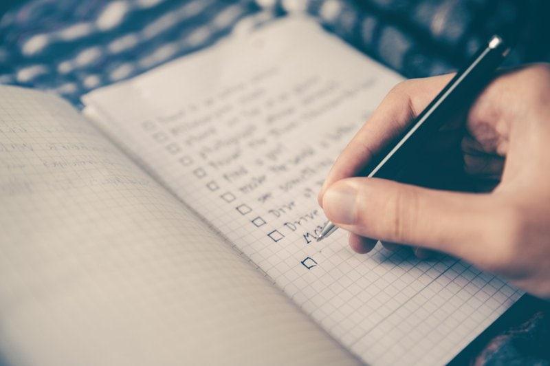ruka držiaca pero vytvára v zošite zoznam povinností