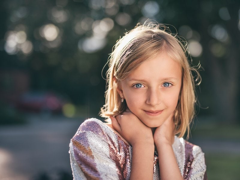 šťastné dievčatko s modrými očami držiace si rukami krk