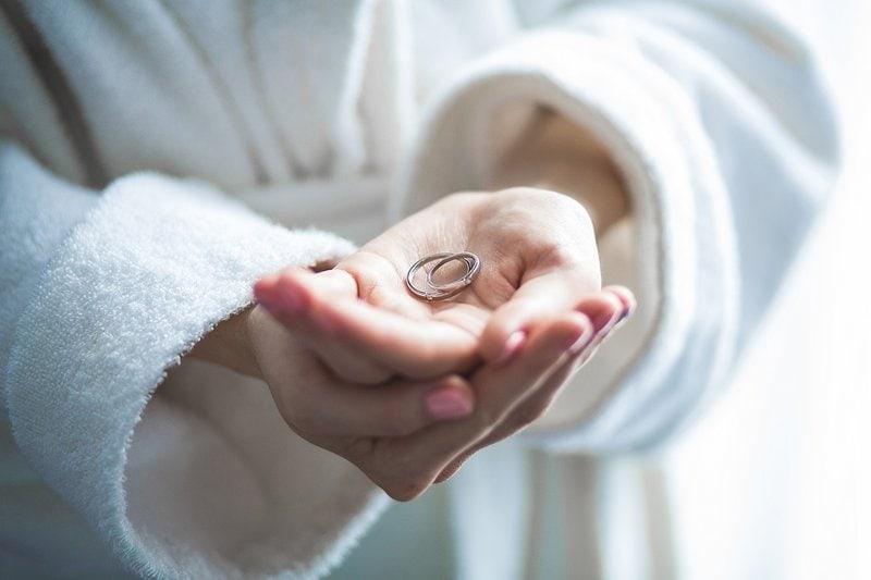 žena v župane drží v rukách diamantový zásnubný prsteň a obrúčku