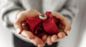 ženské ruky držiace lupene červených ruží na ktorých je uložený prsteň
