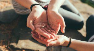 muž drží v spojených dlaniach zásnubný prsteň a ženská ruka sa ho dotýka