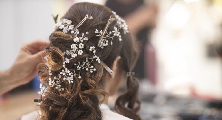 nevesta s hotovým svadobným účesom s ozdobnými sponkami a kvetinami