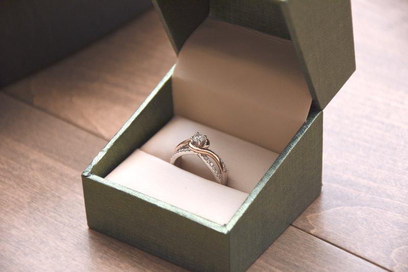 zlatý zásnubný prsteň s veľkým diamantom uprostred a malými postrannými diamantmi v šedej darčekovej krabičke