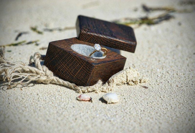 zásnubný diamantový prsteň uložený v drevenej krabičke na piesku