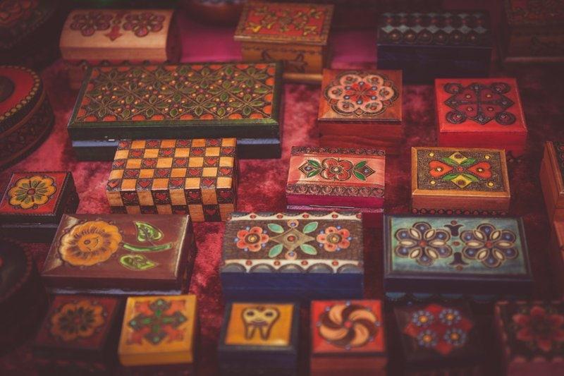 ozdobne dekorované farebné drevené šperkovnice zoradené v piatich radoch na červenej látke
