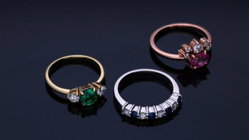 tri prstene z žltého, bieleho a ružového zlata s drahými kameňmi na tmavom pozadí