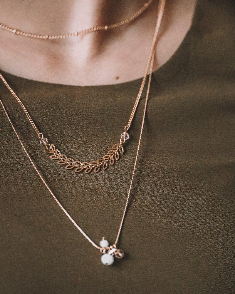 tri zlaté retiazky rôznych dĺžok zavesené na krku a hnedej látke