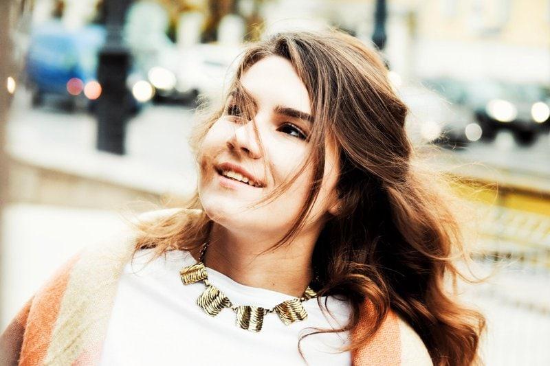 mladá žena s vlnitými hnedými vlasmi a zlatým náhrdelníkom sa usmieva a pozerá dohora