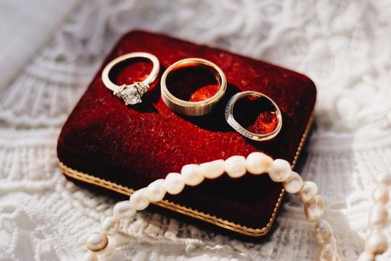 tri prstene a jeden náramok uložené na červenom vankúšiku