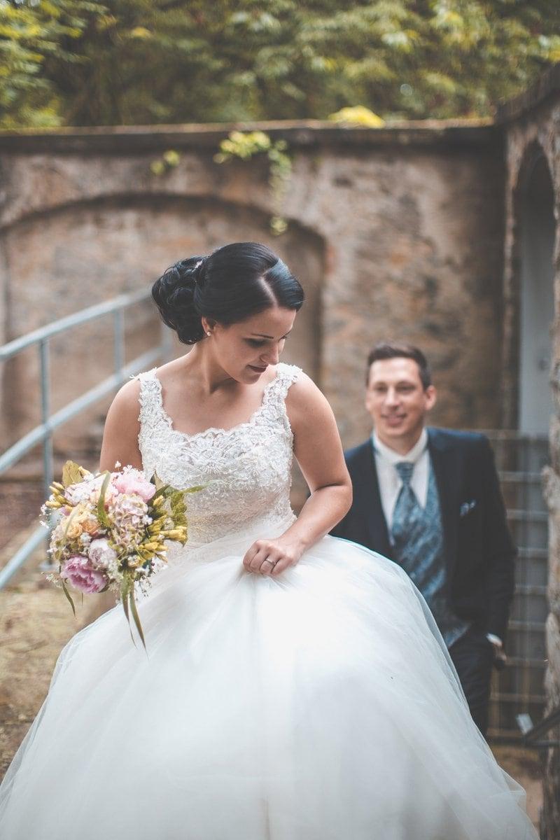 mladá nevesta v svadobných šatách držiaca kyticu