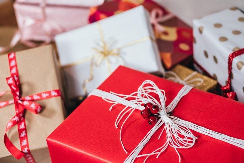 vianočné darčeky zabalené v červenom, zlatom a bielom obale previazané šmúrkami