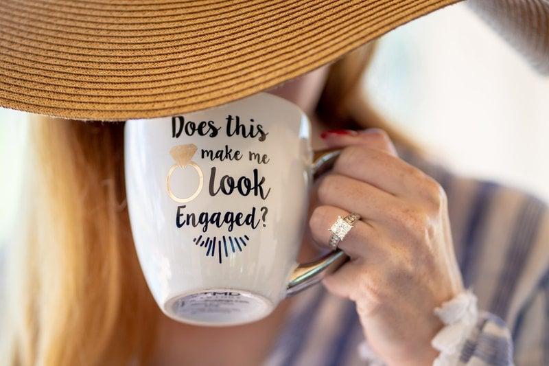 žena s diamantovým zásnubným prsteňom v klobúku drží v ruke biely hrnček s nápisom