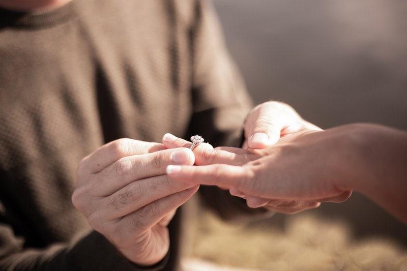 muž drží ruku ženy počas toho ako ju žiada o ruku a nastoká jej diamantový prsteň na prst