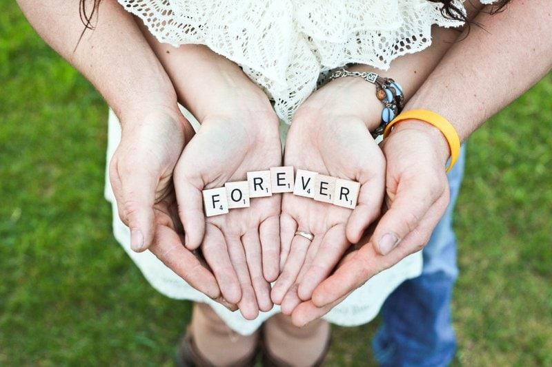 slovo forever vytvorené z kociek scrabble v spojených rukách ženy a muža