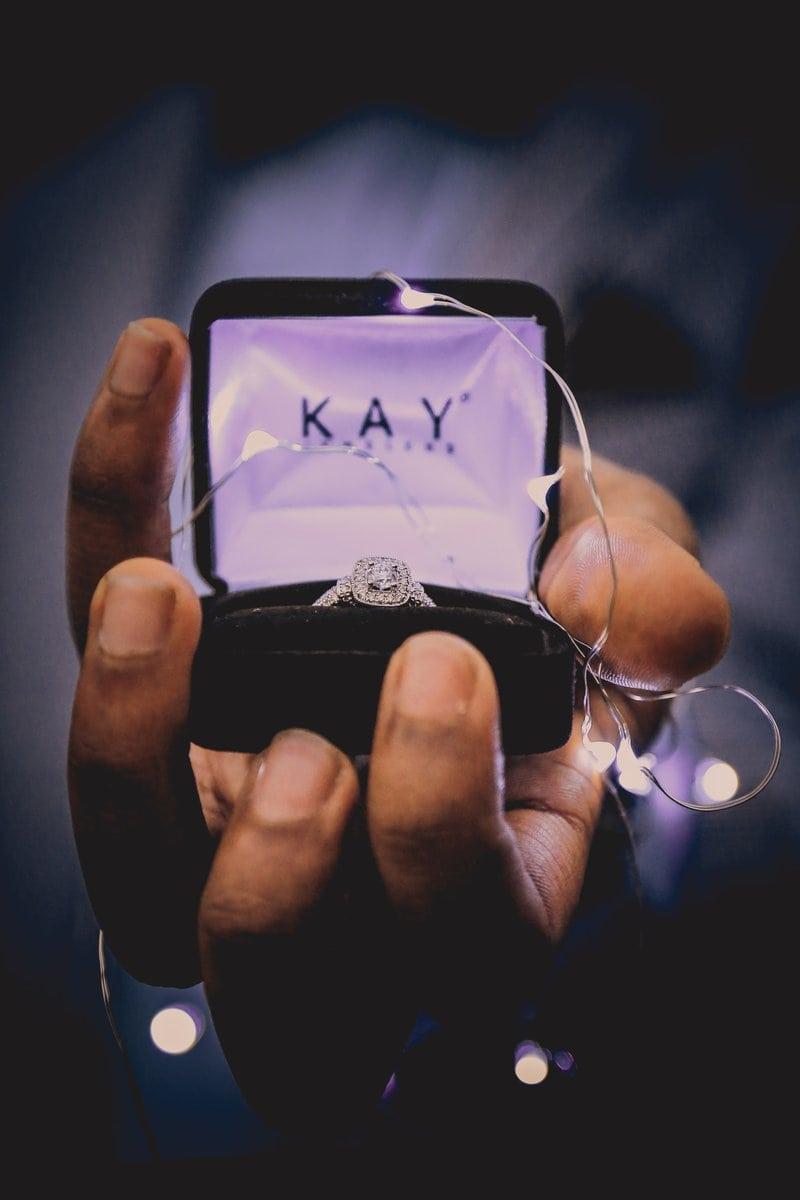 mužská ruka drží zásnubný prsteň v ozdobnej krabičke omotanej svetielkami