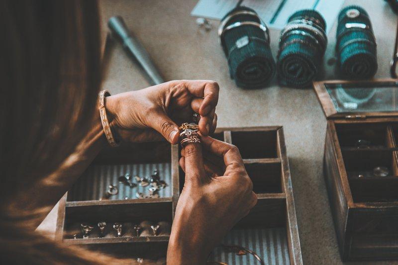 staršia žena drží v ruke tri prstene a pred sebou má drevenú šperkovnicu