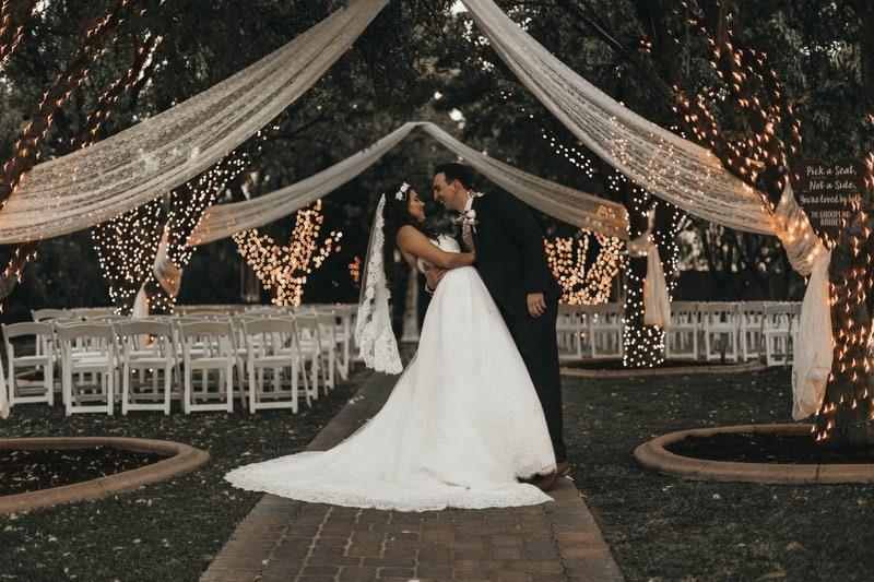nevesta v bielych svadobných šatách so ženíchom stoja v objatí pod výzdobou pod holým nebom