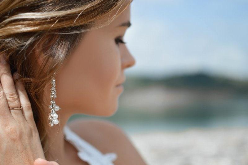 mladá žena s hnedými vlasmi otočená tvárou na bok ukazuje na svoju dlhú diamantovú náušnicu