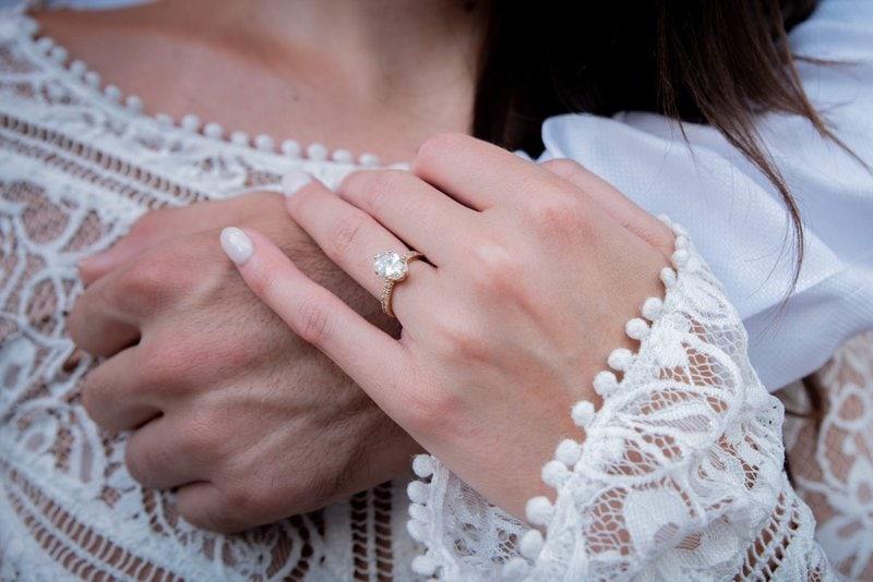 mužská ruka objímajúca ženu a žena s diamantovým prsteňom na prstenníku drží túto ruku