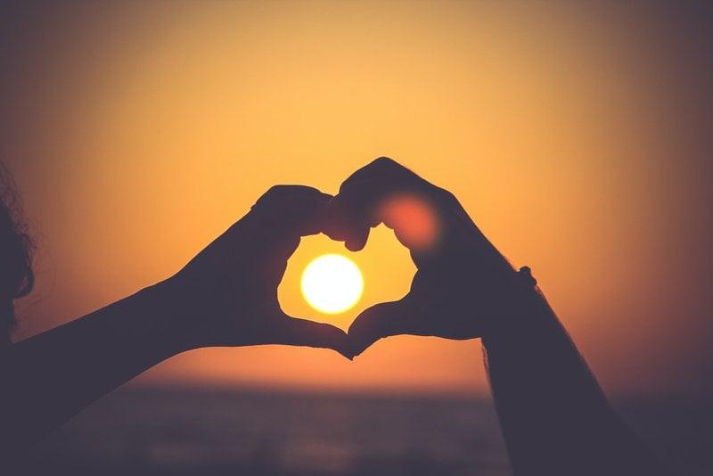 západ slnka cez ruky dvoch zamilovaných ľudí spojených do tvaru srdca