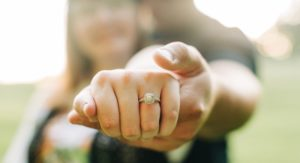 muž objíma žena zozadu držiac jej ruku s detailom na diamantový zásnubný prsteň