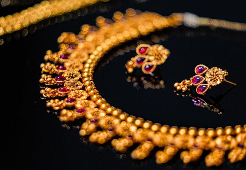 zlatý náhrdelník s náušnicami s ružovými drahokamami položené na čiernom pozadí