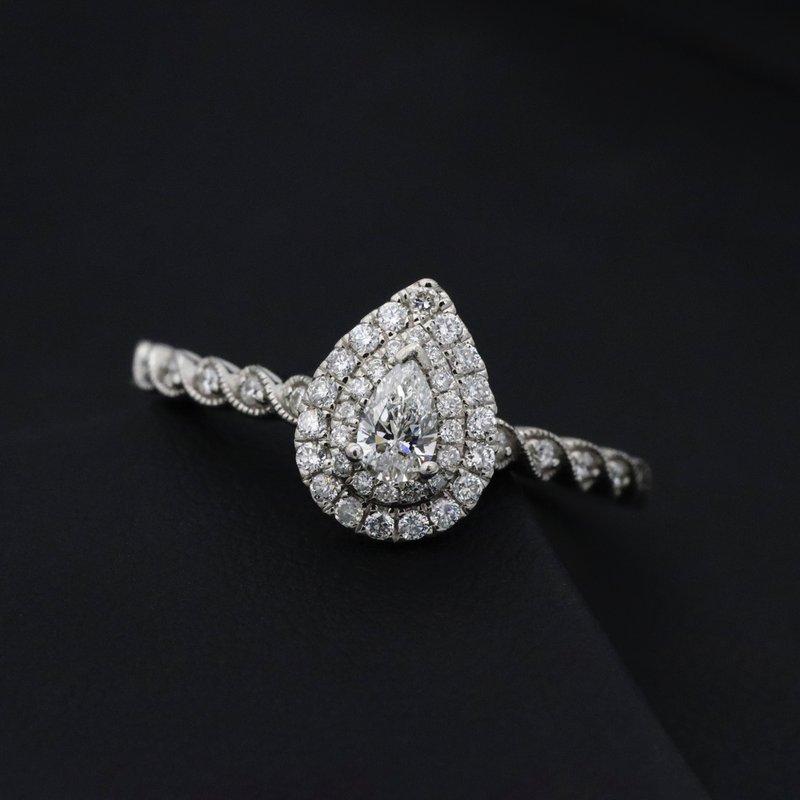 diamantový zásnubný prsteň v tvare pear na tmavom pozadí