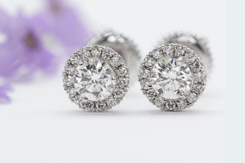dve diamantové náušnice na bielom pozadí s fialovým kvetom na ľavej strane
