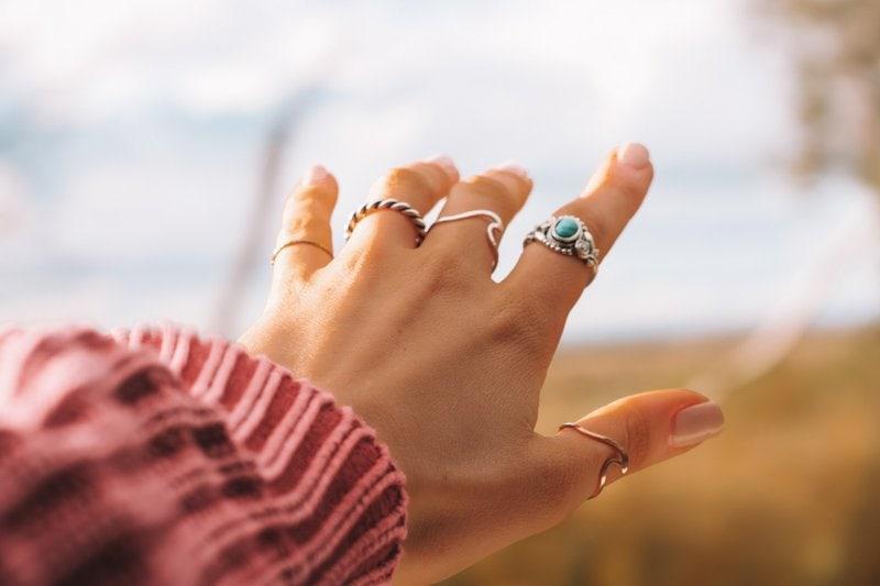 naťahujúca sa ruka s rozličnými prsteňmi na každom prste