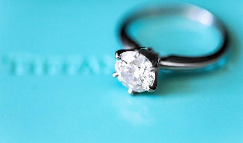 prsteň z bieleho zlata s diamantovým kameňom na svetlomodrom pozadí