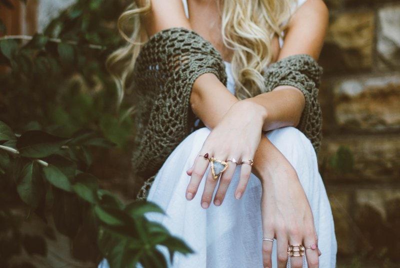 žena sediaca s prekríženými rukami s prsteňmi na prstoch na schodoch vedľa stromu so zelenými listami